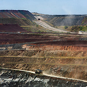 Trucks haul ore out of the terraced earth ringing the crater of a gold mine pit at the Geita Gold Mine.
