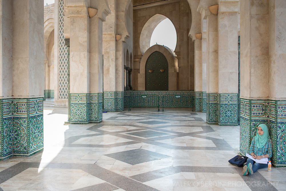 A muslim girl sits to study in the fresh shadow of the marble rich arcades of Hassan II Mosque in Casablanca.