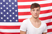 Portrait of young Caucasian man standing against American flag
