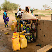 Tabagagi Amadou and her five year-old neice, Laria Idi, while fetching water from a well refurbished by WaterAid in the village of Gadirga in the Commune of Soukoukoutan in the Dosso Region of Niger on 23 July 2013.