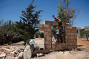 Kids climb up the devastated gate of a small cemetery in Koreen damaged in a heavy shelling of that area before. <br />