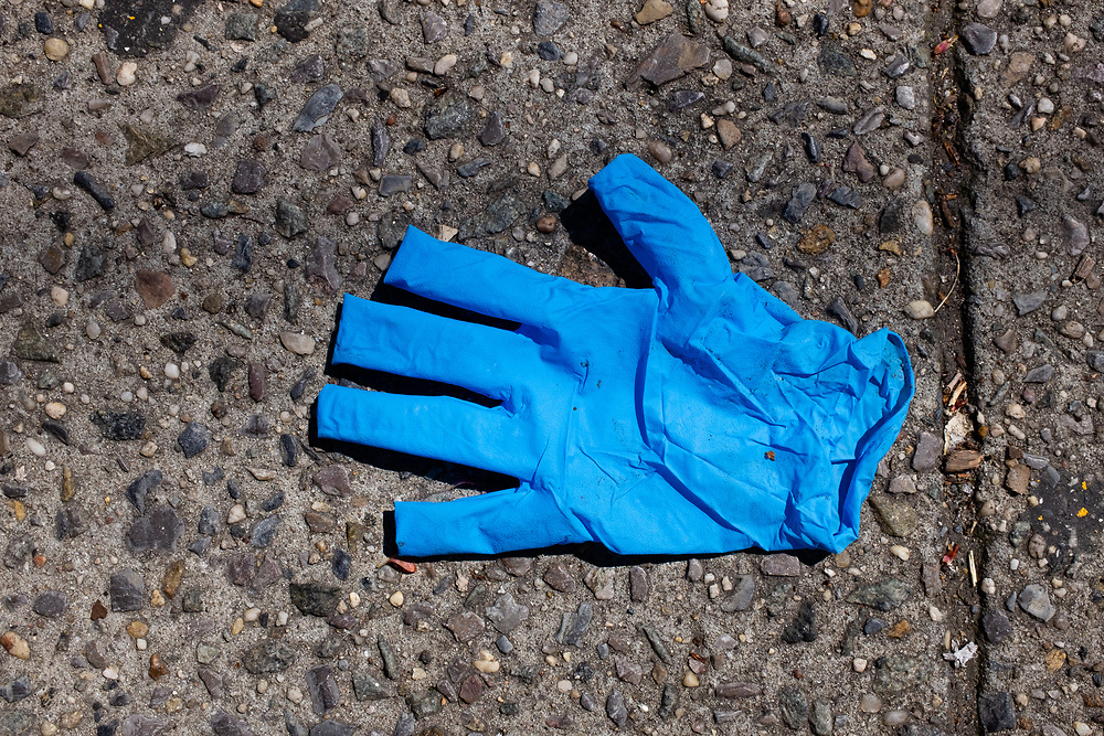 Brooklyn, NY - 15 April 2020. A discarded glove on a sidewalk on Nostrand Avenue is one of many such grim reminders of the effects of COVID-19 on the city.