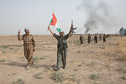 © Licensed to London News Pictures. 11/09/2015. Kirkuk, Iraq. Kurdish peshmerga fighters celebrate after capturing the, previously ISIS held, village of Abo Muhammad during a peshmerga offensive near Kirkuk, Iraq.<br /> <br /> The offensive, which went unchallenged after ISIS left the area ahead of the attack, saw the peshmerga capture 15 villages along the Kirkuk front line. The objective of the offensive was to expand the safety zone around Kirkuk, stopping militants from firing missiles and rockets in to the city of Kirkuk. 3 peshmerga were killed and 24 wounded due to improvised explosive devices left behind by the militants. Photo credit: Matt Cetti-Roberts/LNP