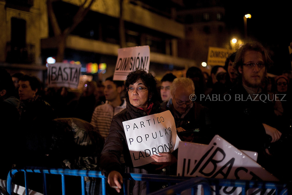 A woman holds a placard reading 'Popular Party Thieves' during a demonstration against political corruption and claiming Mariano Rajoy to resign outside the PP headquarters in Madrid on February 1, 2013. The Spanish Newspaper 'El Pais' published secret papers of income implicating Spanish Prime Minister and other members of the PP (Popular Party). Rajoy's government has denied these secret payments.