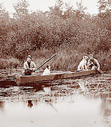Men with dogs duck hunting in a canoe photo circa 1910.