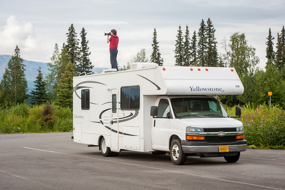 Boy taking photographs of Alaskan landscape while standing on top of an RV