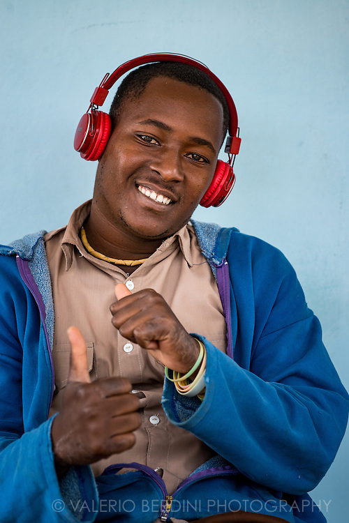 A smiling happy man listening to music through a pair of headphones. Music is an essential part of Cuban life and culture, Cubans are bound to music and get any occasion to listen to and dance to it. Vinales, Cuba 2015.