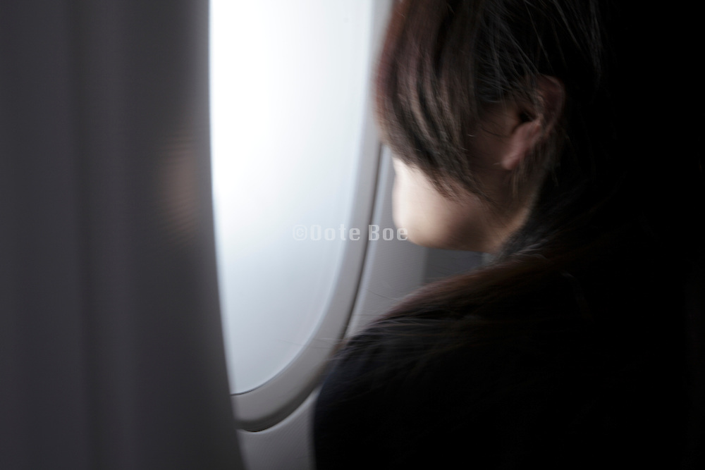 woman looking out of window of airplane