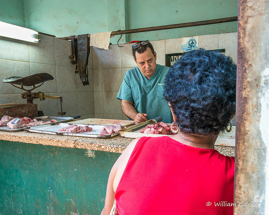 A butcher waits as a customer looks over the meat available in this open air store front. (Havana, Cuba)