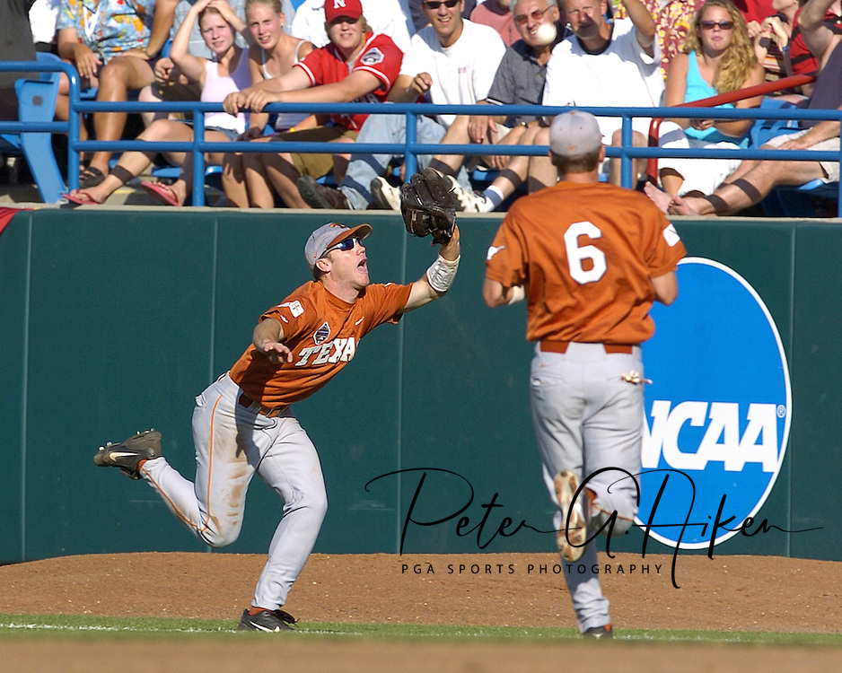 Texas right fielder Nick Peoples (R) races down the right field line to make the catch to end the inning, in front of Longhorn second basemen Roby Hudson (6).  Texas defeated Baylor in the first round of the College World Series 5-1 at Rosenblatt Stadium in Omaha, Nebraska on June 18, 2005.