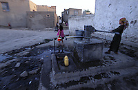 Children pumping water out of the well
