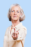 Senior woman in casuals making rebellious hand gesture against blue background