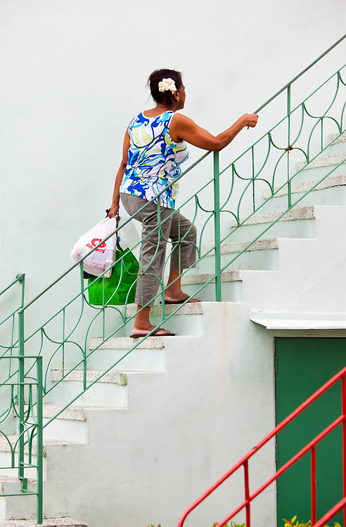 A woman holds Miami Modern railing as she climbs the stairs of a small Miami Beach apartment building