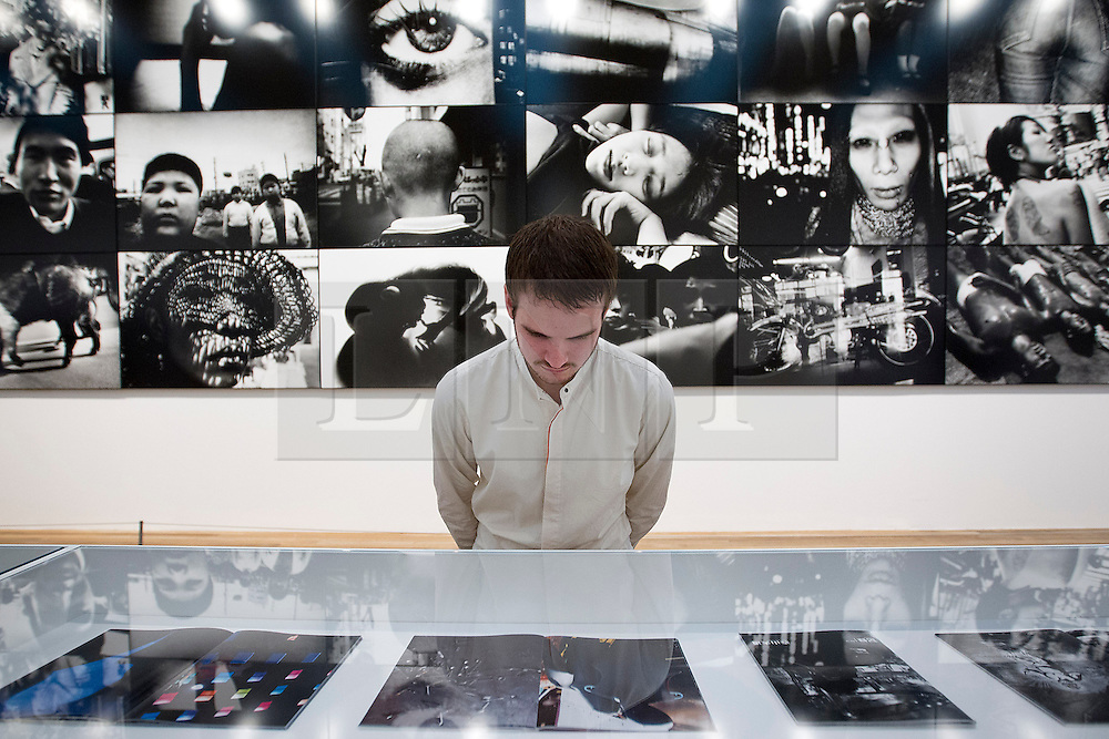 © Licensed to London News Pictures. 08/10/2012. LONDON, UK. A member of Tate staff stands in front of 'Memory 2012' (2012) as he views photo books by artist Daido Moriyama at an exhibition at the Tate Modern in London today (08/10/12). The exhibition, entitled 'William Klein + Dado Moriyama', is the first to examine the relationship between the work of photographer/film maker William Klein (b. 1928) and photographer Dado Moriyama (b. 1938) and opens to the public on the 10th of October 2012.  Photo credit: Matt Cetti-Roberts/LNP