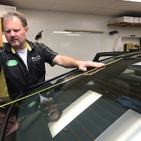 Braun, measures out the back window of a customers car before cutting a piece of window film.