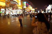 Wangfujing Dajie shopping street and pedestrian zone. Shopping at night. Girls making souvenir photos with a digicam.