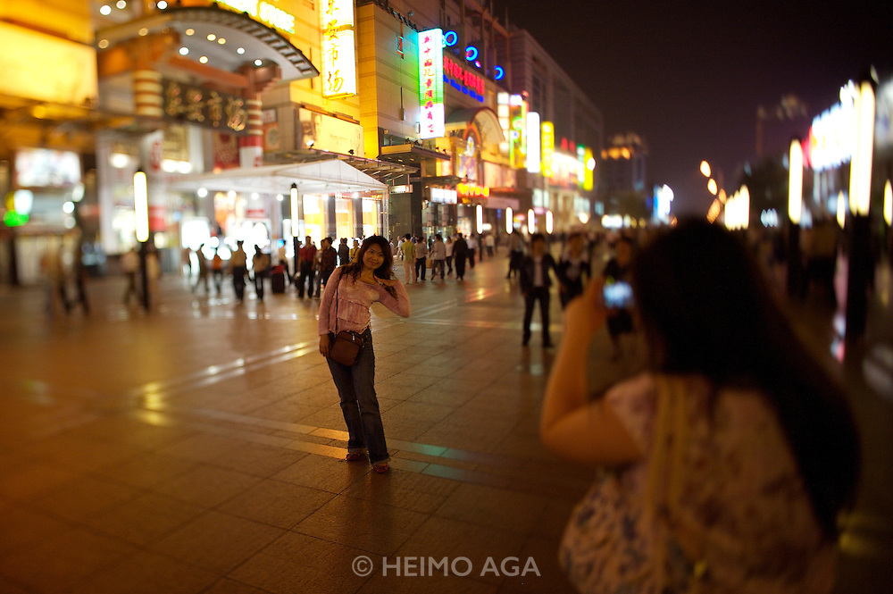Wangfujing Dajie shopping street and pedestrian zone. Shopping at night. Girls making souvenir photos with a digicam.