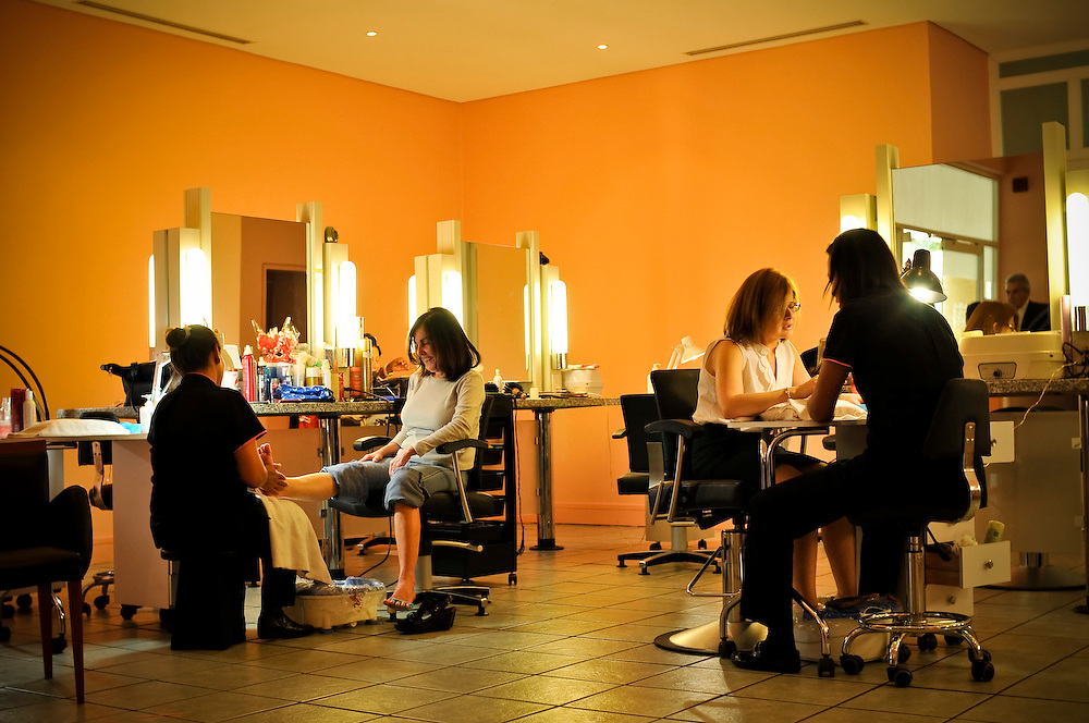 (Left) Laura Vegas, 38, gives Valentina Feo, 54, a pedicure while Maria Alejandra Marchegiani, 30, receives a manicure from Neritza Martinez, 24, at the salon at the Caracas Country Club.  Hundreds of employees at the club fear they will lose their jobs if President Hugo Chávez expropriates the club's land to build apartments for the poor.
