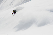 Alex Yoder, Moiwa backcountry, Niseko, Hokkaido, Japan. A brief sunny patch allowed for wide open turns this morning in the back bowls. Yoder obliged and slashed a bank before doing this drawn-out power carve out the bottom.
