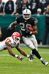 November 7, 2010; Oakland, CA, USA;  Oakland Raiders running back Darren McFadden (20) breaks a tackle from Kansas City Chiefs cornerback Donald Washington (27) during the first quarter at Oakland-Alameda County Coliseum.