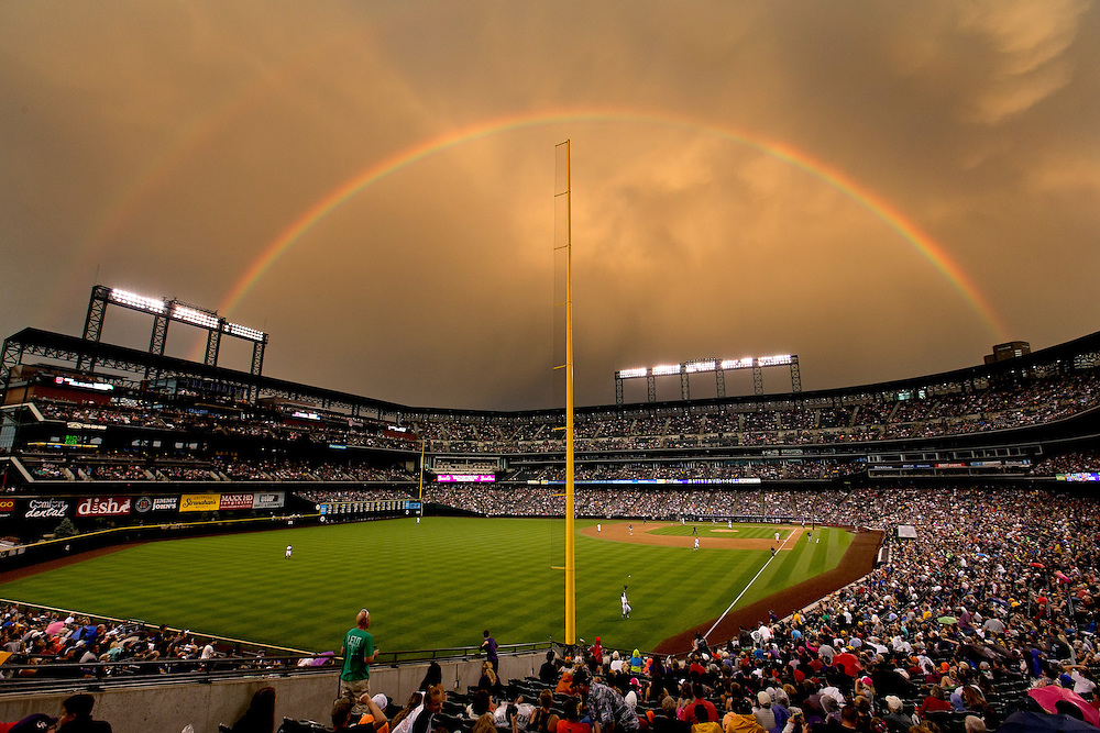 DENVER, CO - JULY 25:  Left fielder Corey Dickerson #6 of the Colorado Rockies makes a catch on a fly ball off the bat of Gaby Sanchez #17 of the Pittsburgh Pirates for the third out of the sixth inning as a double rainbow illuminates the stadium at Coors Field on July 25, 2014 in Denver, Colorado. (Photo by Justin Edmonds/Getty Images) *** Local Caption *** Corey Dickerson; Gaby Sanchez