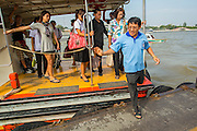 21 NOVEMBER 2012 - BANGKOK, THAILAND: A passenger jumps off a still moving Chao Phraya Express Boat in Bangkok. The Chao Phraya Express boats run up and down the Chao Phraya River in Bangkok providing a sort of bus service for neighborhoods near the river. The boats are the fastest way to get from north to south in Bangkok. Thousands of people commute to work daily on the Chao Phraya Express Boats and fast boats that ply Khlong Saen Saeb. Boats are used to haul commodities through the city to deep water ports for export.    PHOTO BY JACK KURTZ