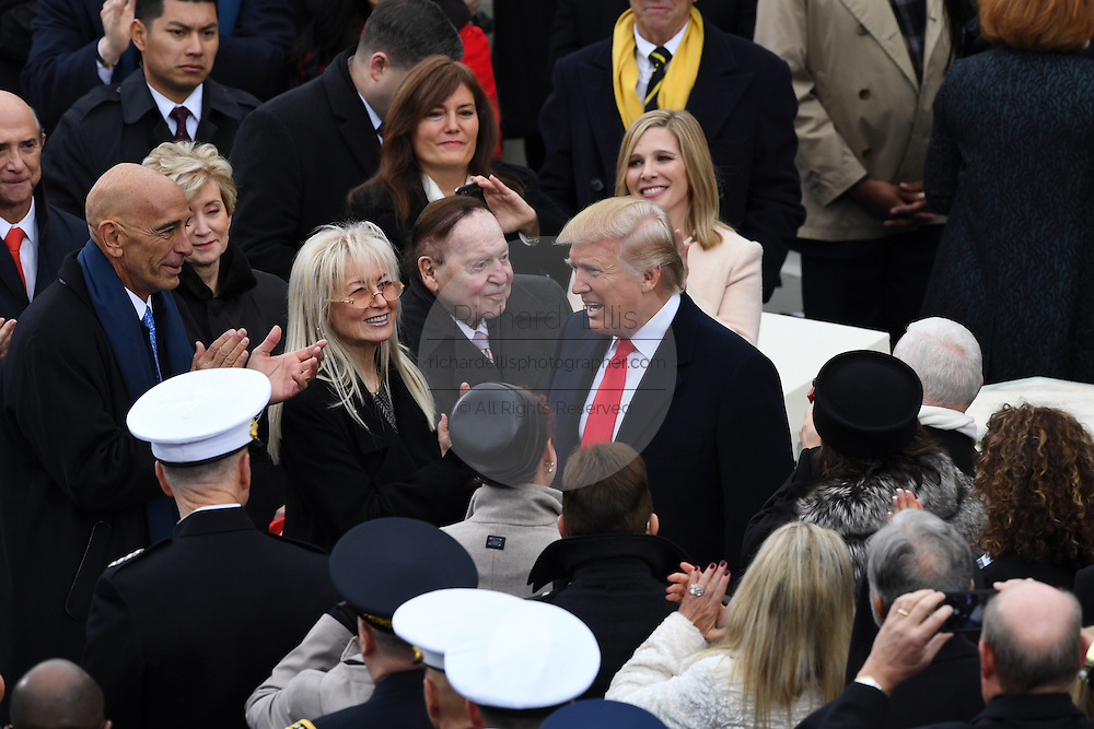 President-elect Donald Trump greets American casino magnate Sheldon Adelson as he arrives for the Inaugural Ceremony to become the 45th President on Capitol Hill January 20, 2017 in Washington, DC.