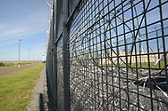 Barbed wire fencing rests outside the facility with Graterford Prison in the background during a tour through the newest prison in Pennsylvania Friday, September 01, 2017 at State Correction Institution Phoenix in Skippack, Pennsylvania. The facility is inching closer to opening, two years late, to replace Graterford Prison at a cost of $400 million. (Photo by William Thomas Cain/CAIN IMAGES)