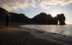 © Licensed to London News Pictures. 05/11/2016. Lulworth, UK.  A man standing on the beach at Durdle Door on the Jurassic Coast in Dorset this morning, 5th November 2016.  Photo credit: Rob Arnold/LNP