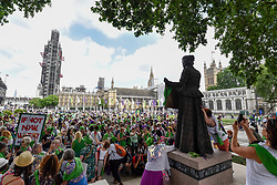 "© Licensed to London News Pictures. 10/06/2018. LONDON, UK.  Women gather around the statue of Millicent Fawcett in Parliament Square.  Over 40,000 women and girls take part in ""Processions"", a mass participation artwork to celebrate one hundred years of votes for women.  Walking together from Park Lane to Westminster participants wear either green, white or purple scarves representing the colours of the Suffragette movement.  Similar walks took place in Belfast, Cardiff and Edinburgh.  Photo credit: Stephen Chung/LNP"