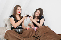 Young women toasting with wine glasses in bed
