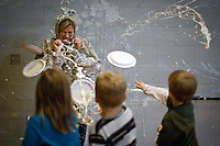 JEROME A. POLLOS/Press ..Principal Katrina Kelly takes an onslaught of whip cream pies Thursday from students at Mullan Trail Elementary in Post Falls. Eleven students who were the top sellers in their school's $19,000 fundraiser earned the privilege throw a pies at their principal.