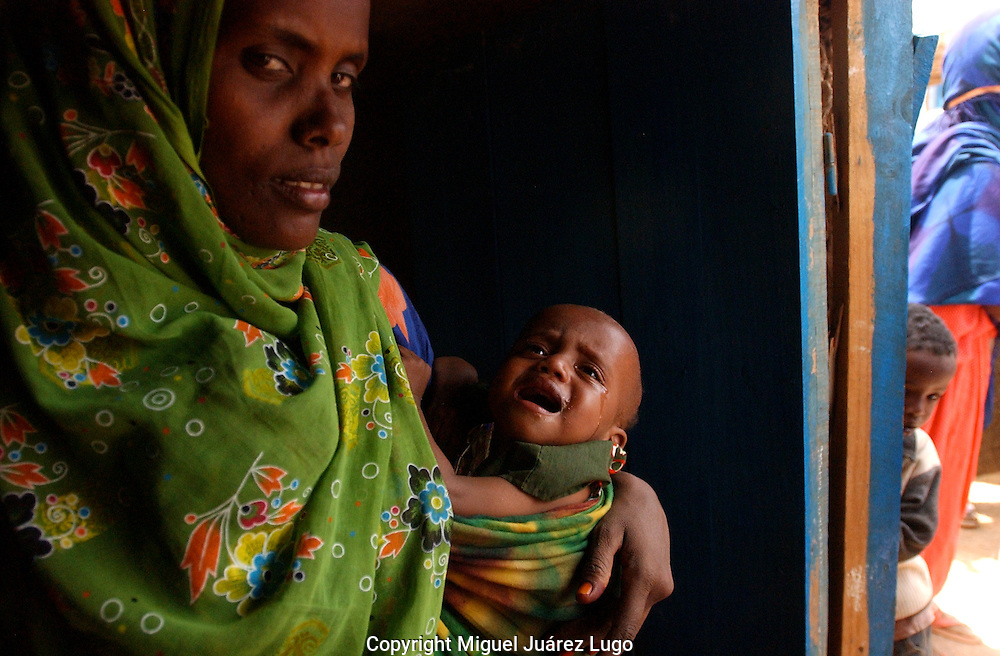 El Barde, Somalia.  A women and her baby, stand on the shade as they wait to see a doctor in a health clinic run by the World Food Programme in El Barde, Somalia, that is suffering one of the worst drought registered on history.  (PHOTO: MIGUEL JUAREZ LUGO)
