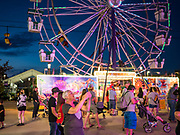 14 AUGUST 2019 - DES MOINES, IOWA: A woman uses her smart phone to take a photo of the children's midway at the Iowa State Fair. The Iowa State Fair is one of the largest state fairs in the U.S. More than one million people usually visit the fair during its ten day run. The 2019 fair run from August 8 to 18.               PHOTO BY JACK KURTZ