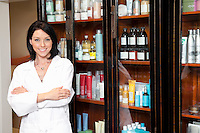 Portrait of a beauty salon employee standing with arms crossed and cosmetics in background