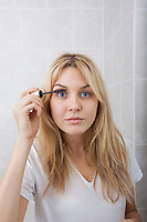 Portrait of young woman applying mascara in bathroom