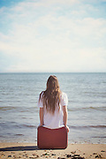 a girl is sitting on a red suitcase at the sea