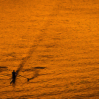 A lone boater skims across the surface of the Potomac River at sunset in Washington Tuesday, Oct. 8, 2013. (AP Photo/J. David Ake)