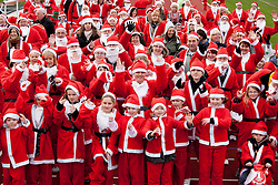© Licensed to London News Pictures. 11/12/2011, Nuneaton, Warwickshire, UK. Over 200 people dressed in Santa outfits ran a mile to raise money for the Mary Evans Hospice appeal earl;ier today. The charity raised over four thousand pounds last year and organiser Janet Kavangah from the hospice said they were hoping to better that this year. Pictured, the santas warm up for the event. Photo credit : Dave Warren/LNP