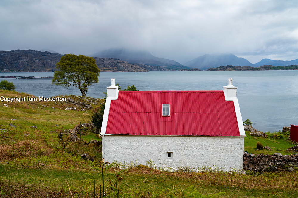 White cottage with red roof in Torridon on the North Coast 500 scenic driving route in northern Scotland, UK