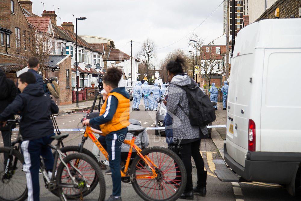 Local residents and media survey the scene as forensics investigators conduct a fingertip search in Chalgrove Road, Tottenham, North London, where a seventeen year-old girl was shot dead on the evening of April 2nd. London, April 03 2018.