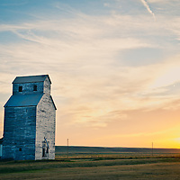 sun sets behind an old grain building on the prairie of montana