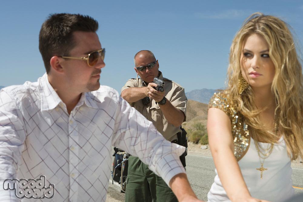 Police man aiming gun at young couple
