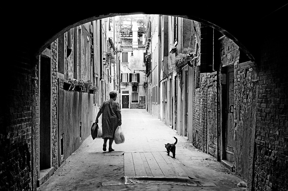 Black and white photo of woman and cat in Venice.