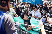 A woman is treated for heatstroke while awaiting the funeral procession of King Bhumibol on June 14, 2016 in Bangkok, Thailand. Thailand's King Bhumibol Adulyadej, the world's longest-reigning monarch, died at the age of 88 in Bangkok's Siriraj Hospital on Thursday after his 70-year reign. Prime Minister Prayut Chan-ocha made a statement Thailand would hold a one-year mourning period as the Crown Prince Maha Vajiralongkorn confirmed that he would perform his duty as heir to the throne.