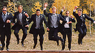 Groom and groomsmen jumping of a wall.