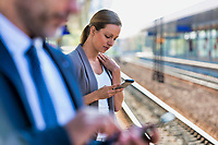 Portrait of businesswoman using smartphone while waiting for the train in station