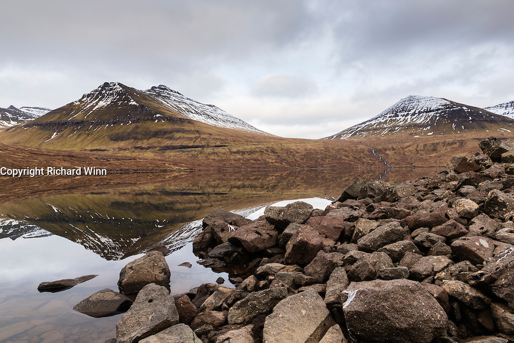 On the bank of Eiðisvatn, with reflections of the surrounding mountains in the water.