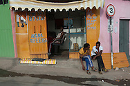 Young men sit in front of a barber shop waiting for customers in Harar, Ethiopia.