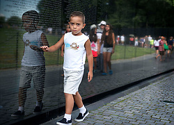 Young boy at Vietnam Memorial. The names of young soldiers who were killed in that war are engraved in the stone over his shoulder.